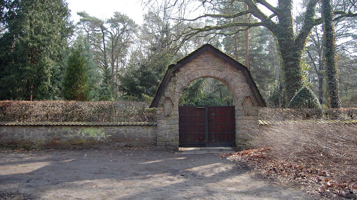 Der Eingang des Friedhofs Grunewald-Forst. Ohne die drei Wegweiser würden Besucher den Ort wohl nicht finden.